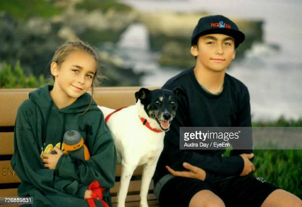 Portrait Of Siblings Sitting With Dog On Bench