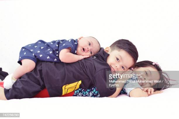Portrait Of Siblings Stacking On Bed Against White Background