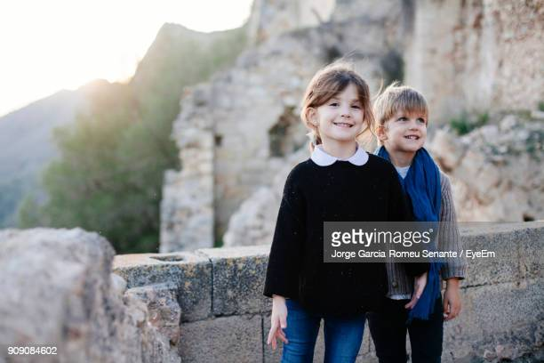 Portrait Of Siblings Standing Against Stone Wall