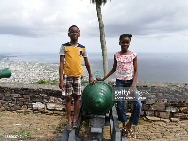 portrait of siblings standing by cannon against sea - port of spain stock photos and pictures