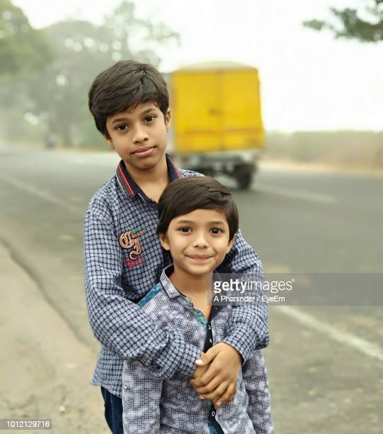 Portrait Of Siblings Standing By Road