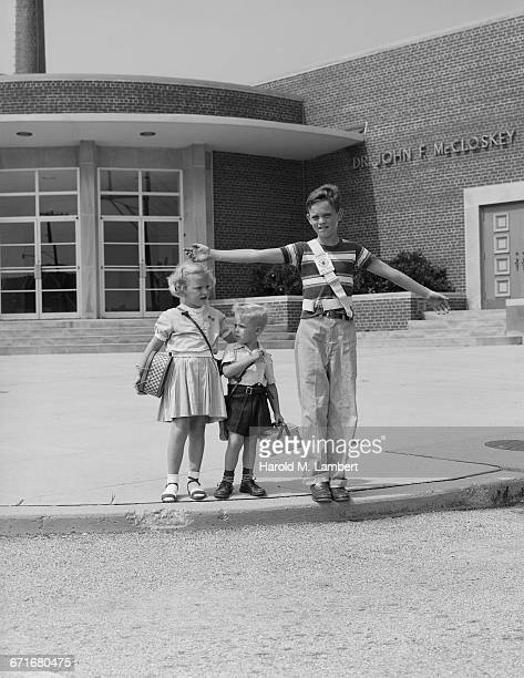 Portrait Of Siblings Standing In Front Of School