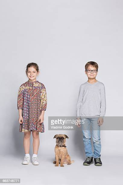Portrait of siblings with dog against white background