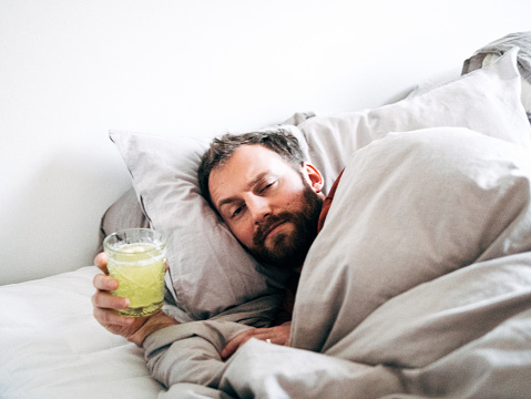 Portrait Of Sick Man Holding Drink While Lying On Bed At Home - gettyimageskorea