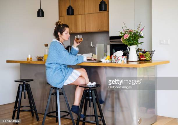 portrait of sick mature woman sitting indoors in kitchen, using laptop. - pajamas stock pictures, royalty-free photos & images
