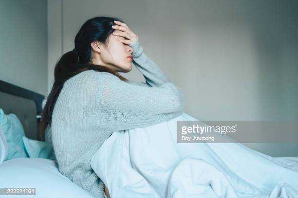 portrait of sickness woman sitting alone on the bed in the bedroom, self isolation herself during coronavirus pandemic outbreak. - 身体症状 ストックフォトと画像