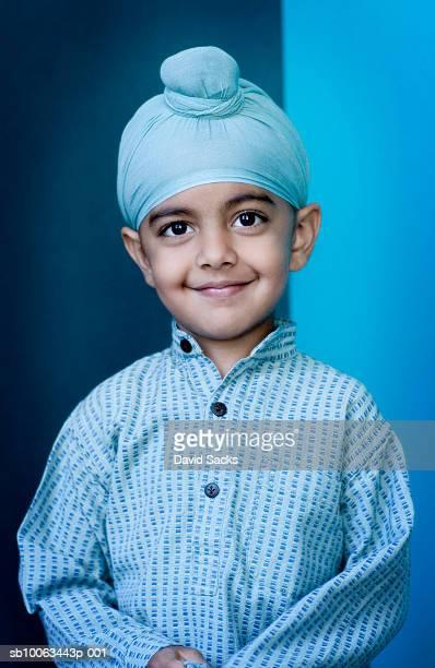 Portrait of Sikh boy (4-5) in turban, smiling