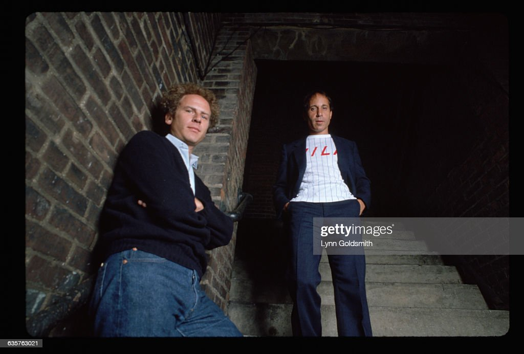 Portrait of Simon and Garfunkel. They are shown in a low-angle view, standing next to a brick wall. Photograph, 1981.