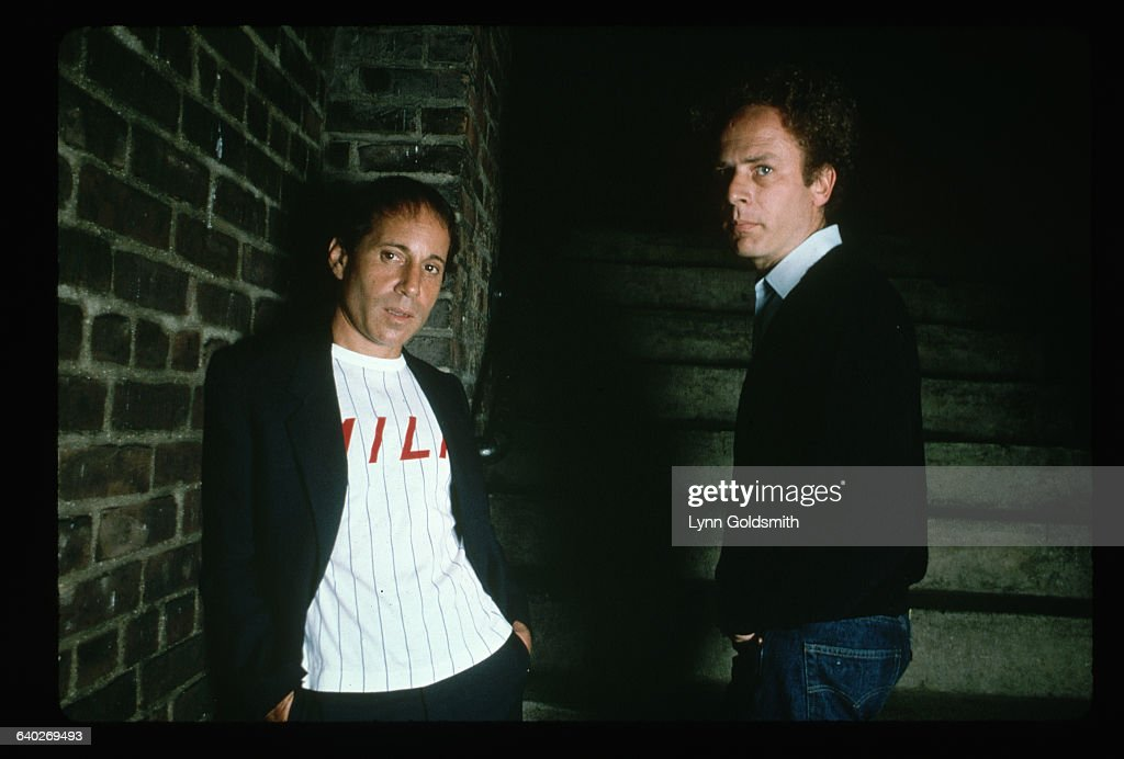 Portrait of Simon and Garfunkel. They are shown waist-up, posing against a brick wall. Photograph, 1981.