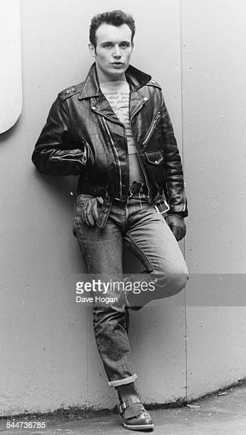 Portrait of singer Adam Ant leaning against a wall wearing jeans and a leather jacket September 12th 1984
