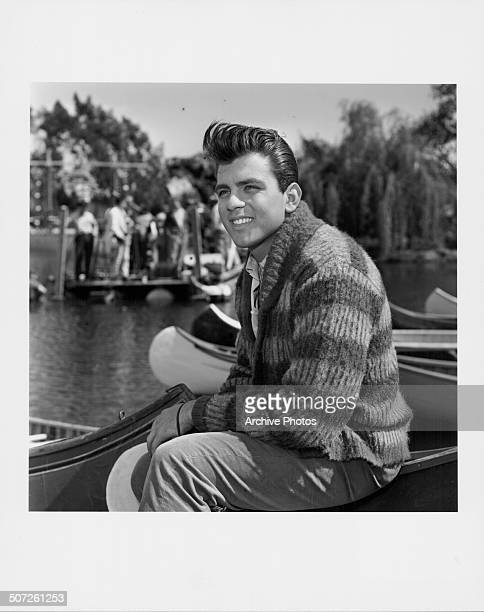 Portrait of singer and actor Fabian Forte sitting on a dock surrounded by canoes wearing a striped sweater circa 1960