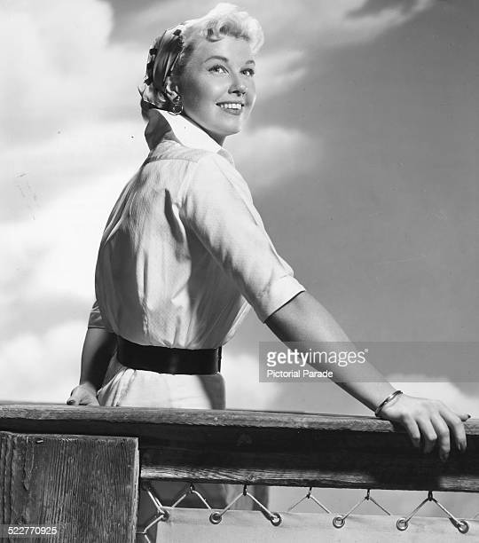 Portrait of singer and actress Doris Day leaning on a fence post and staring into the distance circa 1955