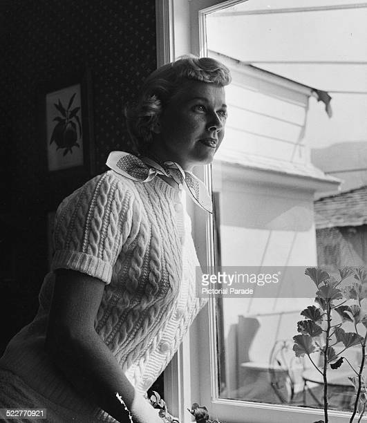 Portrait of singer and actress Doris Day wearing a sweater and a neck scarf and looking out of a window circa 1955