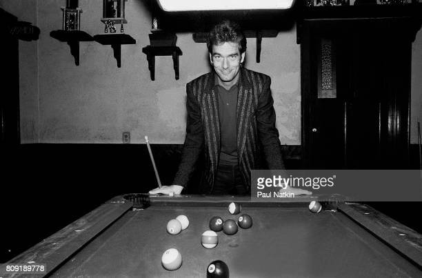 Portrait of singer Huey Lewis standing at a pool table at an unidentified sports bar in Chicago Illinois November 10 1983