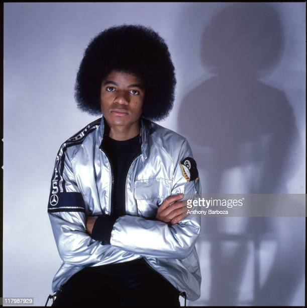 Portrait of singer Michael Jackson dressed in a shiny silver jacket and with arms crossed in November 1977