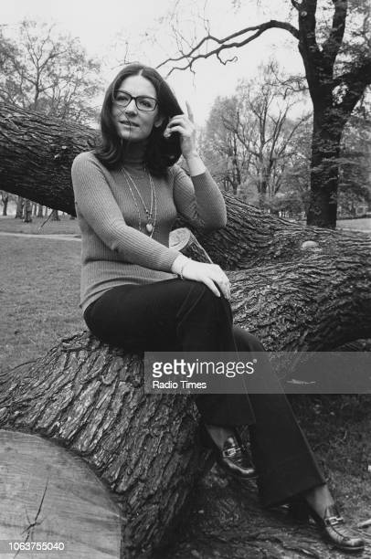 Portrait of singer Nana Mouskouri sitting on a tree trunk in a park, April 1974.