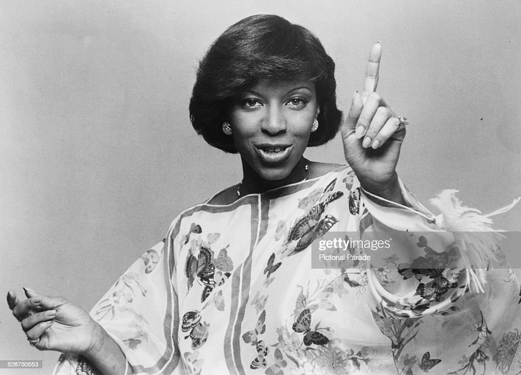 Portrait of singer Natalie Cole, pointing her finger and smiling, wearing a dress with a flower and butterfly pattern, circa 1975.