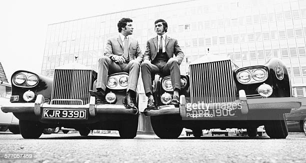 Portrait of singers Tom Jones and Engelbert Humperdinck sitting on the bonnets of two Rolls Royce cars as they celebrate the announcement of a...
