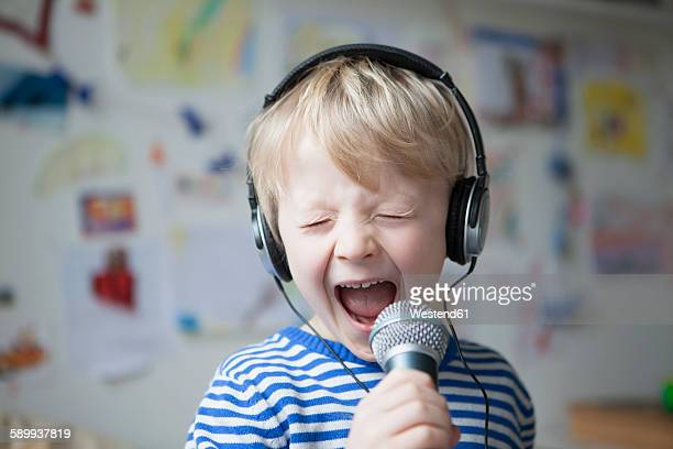 Portrait of singing little boy with headphones and microphone