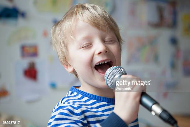 Portrait of singing little boy with microphone