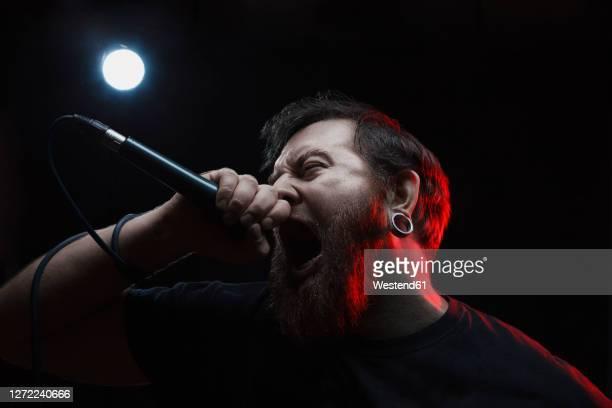 portrait of singing rocker - gesangskunst stock-fotos und bilder