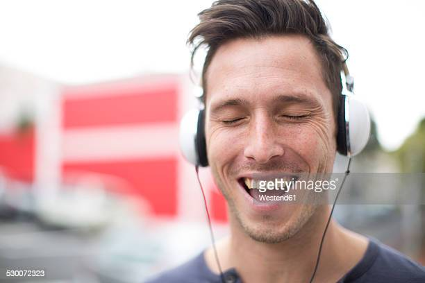 Portrait of singing young man listening music with headphones