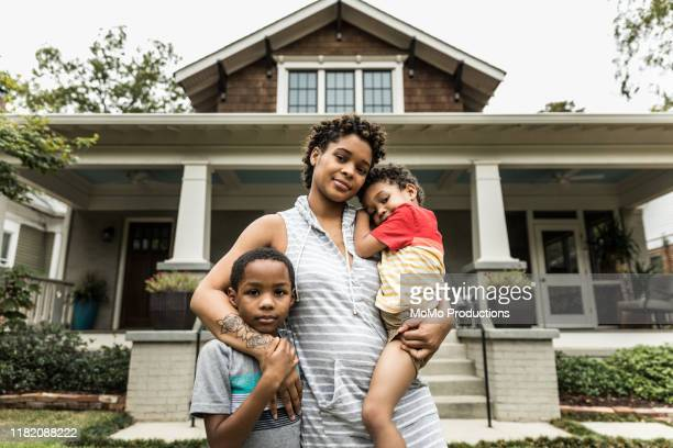 portrait of single mother with young sons in front of house - love stock pictures, royalty-free photos & images