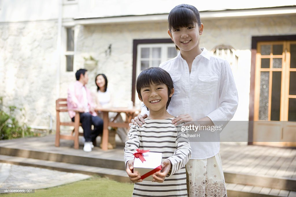 Portrait of sister (12-13) and brother (6-7) with gift outside house : Stockfoto