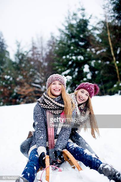 portrait of sisters having fun in snow - sister stock pictures, royalty-free photos & images