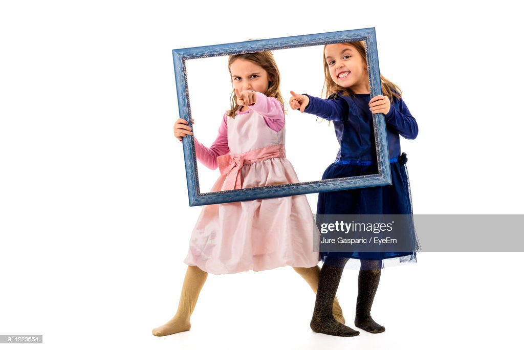 Portrait Of Sisters Holding Frame While Standing Against White ...