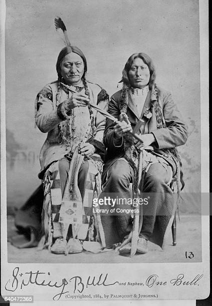 A portrait of Sitting Bull the Hunkpapa Sioux Indian who lead his people to battle against General Custer holding a peace pipe with a friend