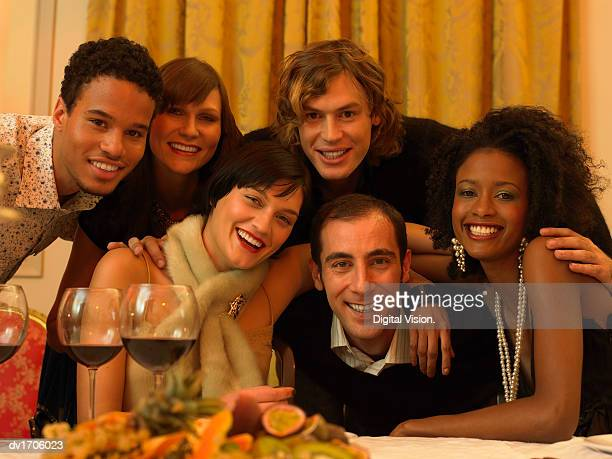 Portrait of Six Smiling Men and Women in Evening Wear Huddled Together at a Dining Table