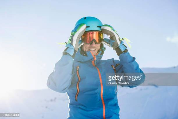 Portrait of skier, adjusting goggles