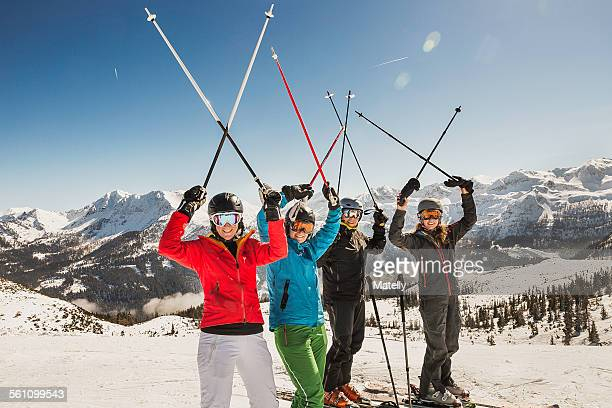 Portrait of skiers on slope, holding ski poles in the air