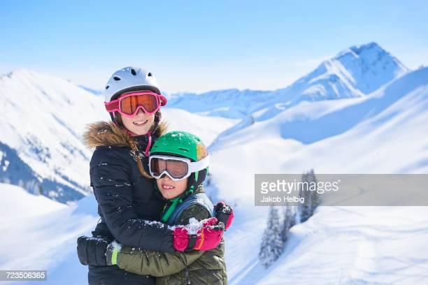 Portrait of skiing teenage girl and brother hugging in Swiss Alps, Gstaad, Switzerland