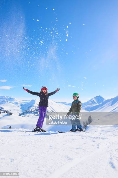 Portrait of skiing teenage girl and brother throwing powder snow in Swiss Alps, Gstaad, Switzerland