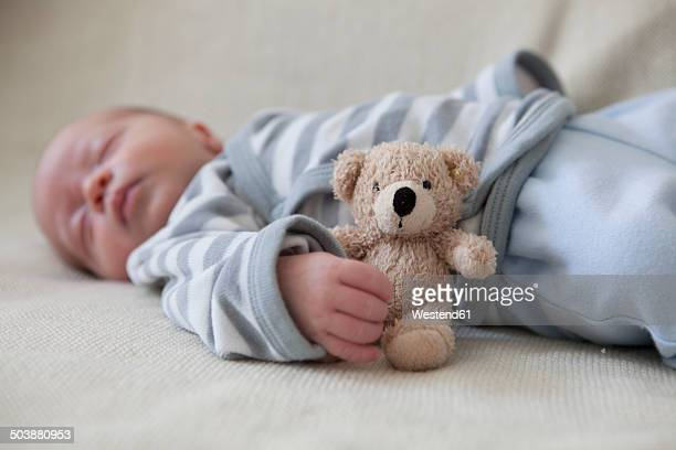 Portrait of sleeping baby boy lying on blanket with teddy