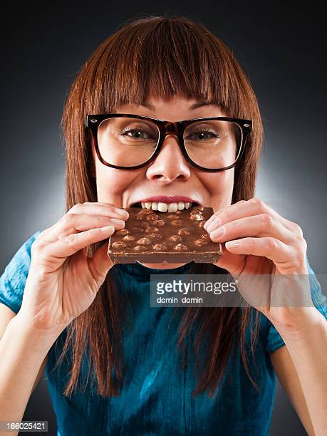 Portrait of slim woman eating chocolate with nuts, studio shot