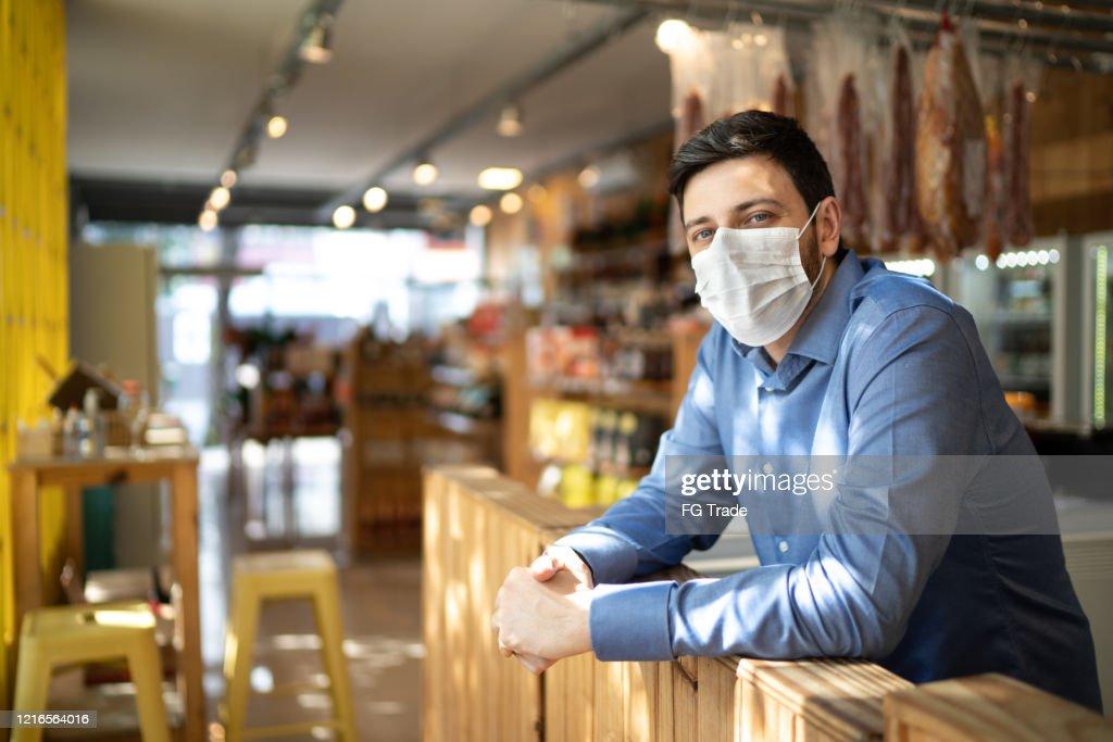 Retrato do dono de pequeno empresário com máscara facial : Foto de stock