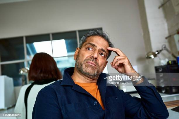 portrait of small business owner with hand on head thinking - thinking outside the box englische redewendung stock-fotos und bilder