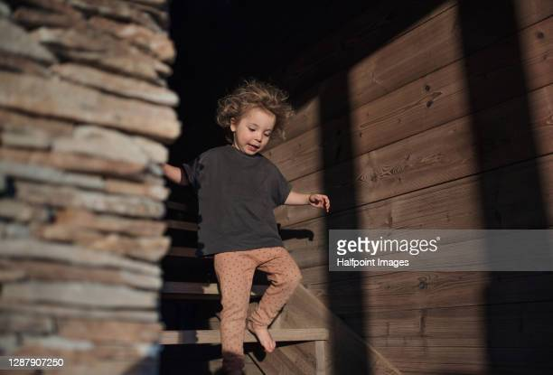 portrait of small girl on holiday in nature, walking on staircase in cottage. - 石造りの家 ストックフォトと画像