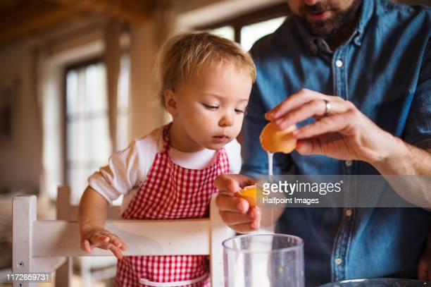 a portrait of small toddler girl in kitchen indoors, baking with father. - baking stock pictures, royalty-free photos & images