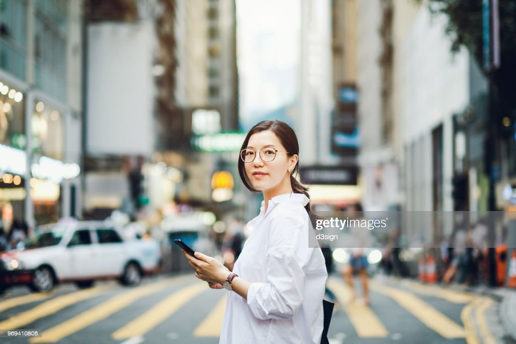 Portrait of smart Asian businesswoman using mobile phone in busy downtown city street : Stock-Foto
