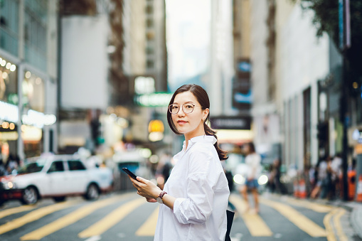 Portrait of smart Asian businesswoman using mobile phone in busy downtown city street - gettyimageskorea
