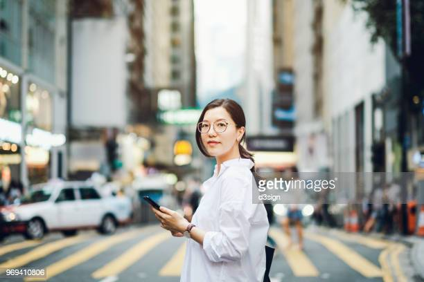 portrait of smart asian businesswoman using mobile phone in busy downtown city street - asien stock-fotos und bilder