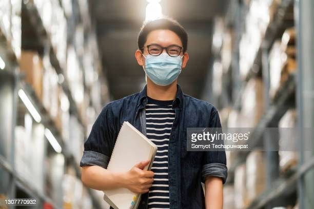 portrait of smart asian male business owner wear mask inspector hand hold paper chart inventory checking smile confident with background of warehouse and cardboard box pallet of product stock - protective workwear stock pictures, royalty-free photos & images