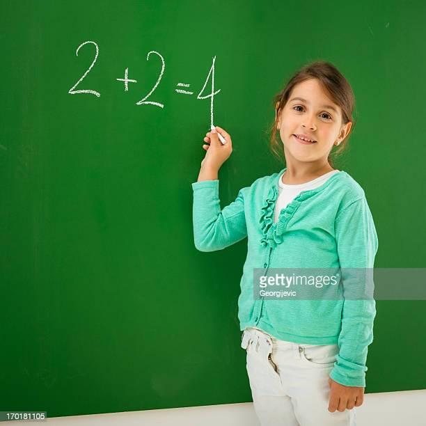 Portrait of smart schoolchild standing at blackboard