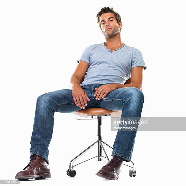 Portrait of smart young man sitting comfortably on chair against white background