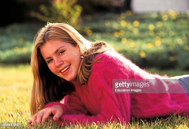 Portrait Of Smiling 14 Year Old Girl Lying In Grass