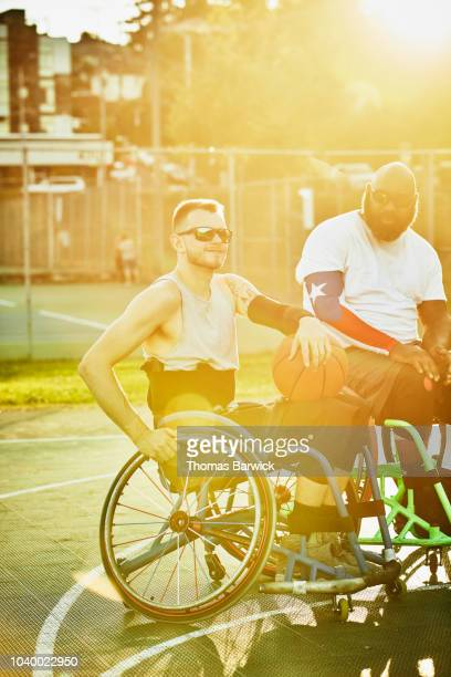 Portrait of smiling adaptive athlete on court after basketball game with friends